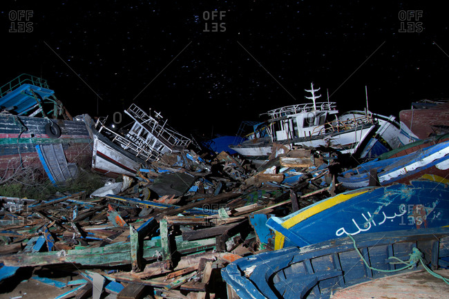 Wooden boats in a ship graveyard at night
