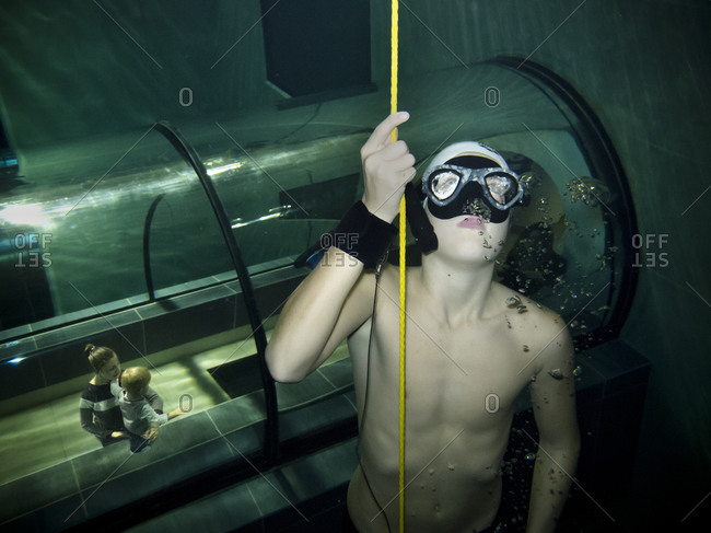 Padua, Italy - December 9, 2014: Man swimming in Y-40, the deepest pool in the world, with an observation tunnel beneath him