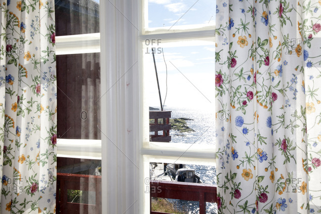 Coastal scene viewed through a window with floral curtains