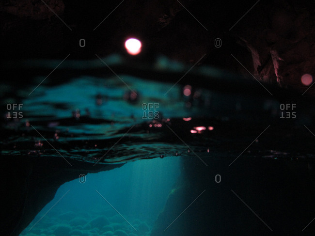 Light shining beneath the surface in an underwater cave
