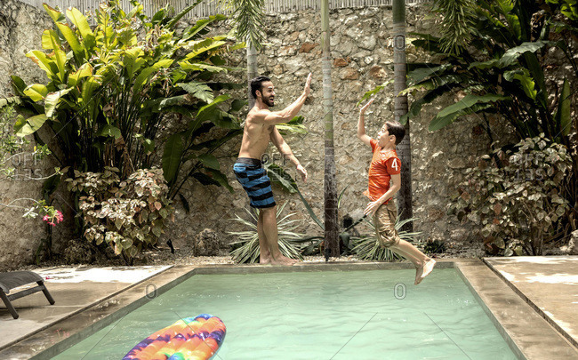 Man and boy midair jumping in pool