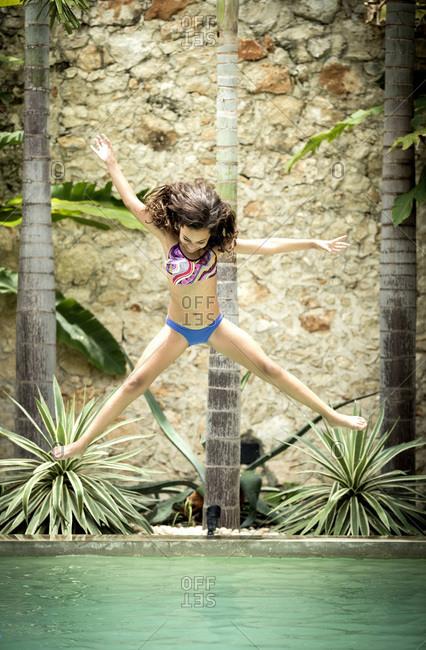 Girl in midair jump into pool