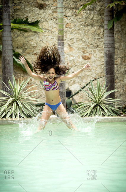 Girl in midair leap into pool