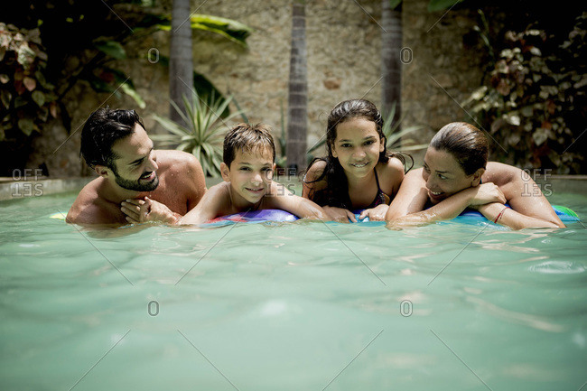 Family of four on floatie in pool together