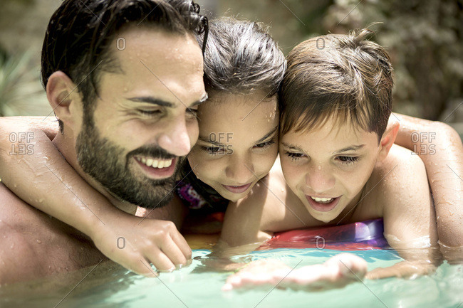 Man and three kids watching hand in pool