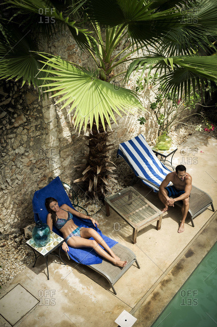 Couple lounging poolside on deck chairs
