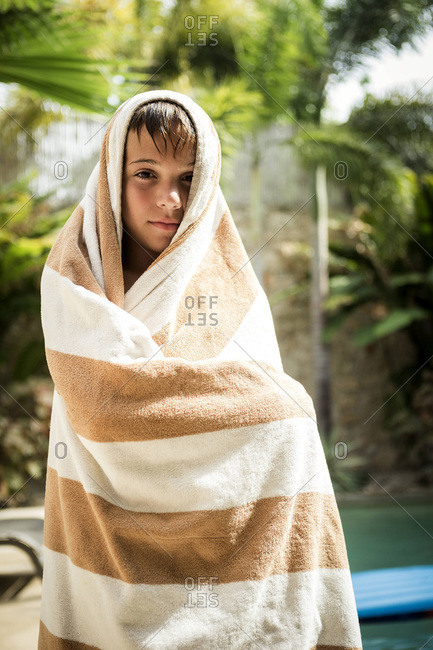 Boy wrapped in towel drying off poolside