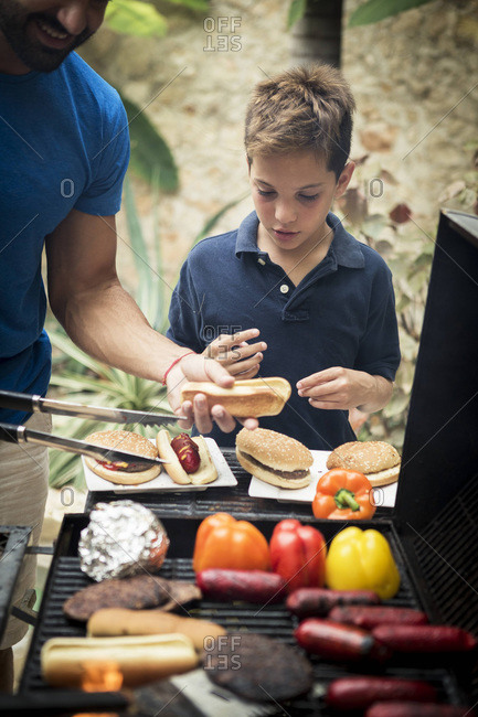 Boy and dad making burgers and hot dogs at grill