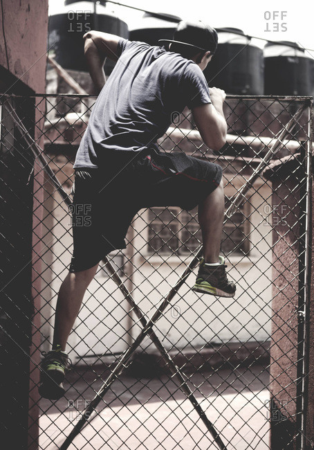 Athletic young man climbing over a fence
