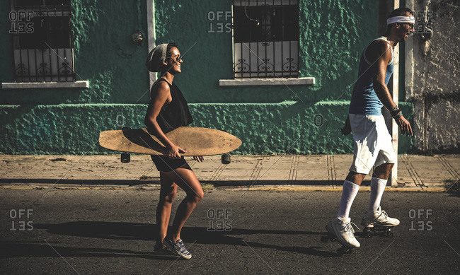 Man and woman with longboard and roller skates