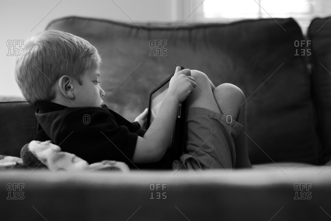 Boy relaxing with a smart tablet