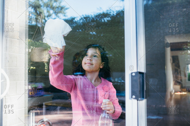 Girl cleaning a glass door at her house