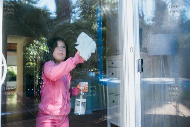 Girl washing windows at her house