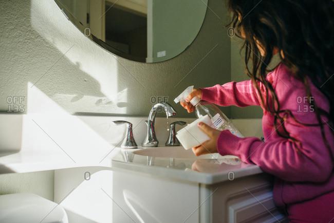 Girl cleaning a bathroom sink