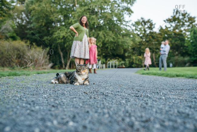 Family outdoors with their pet cat