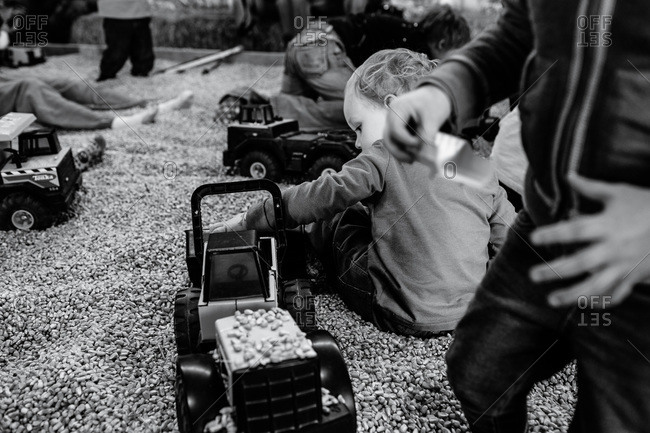 Children playing with trucks in a corn kernel box