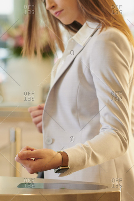 Woman scanning her smart watch in a business lobby
