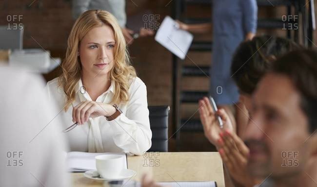 Woman listening during a business meeting at a conference table