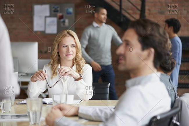Businesswoman listening during a meeting around a conference table