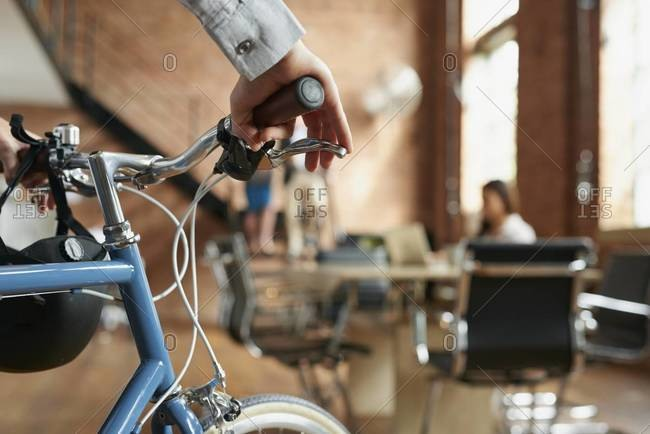 Hands of a man holding a bicycle in a modern business office