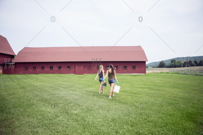Two young women carrying buckets toward a large red barn