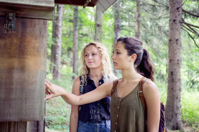 Two young women looking at a hiking map in a park