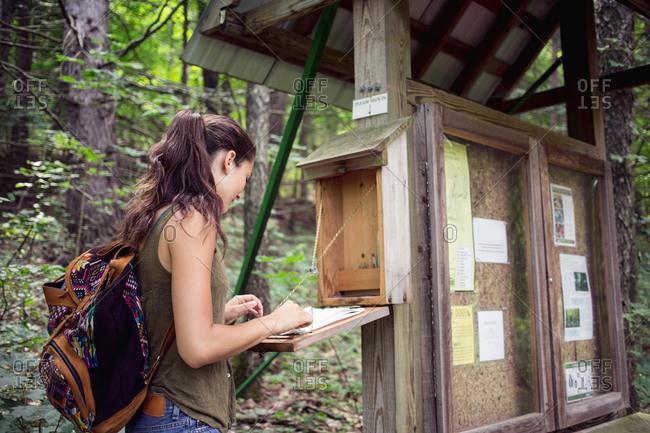 Young woman signing a guest book before a hike