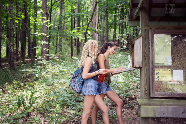 Two young women signing a guest book before a hike