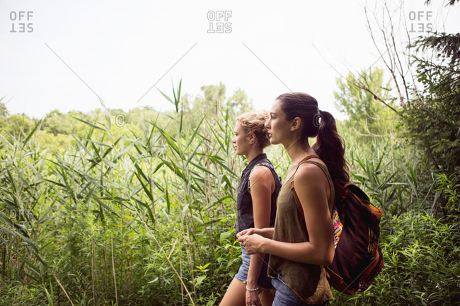 Two young women walking on a trail beside high grasses
