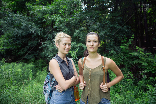 Two young women standing together on a hiking trail