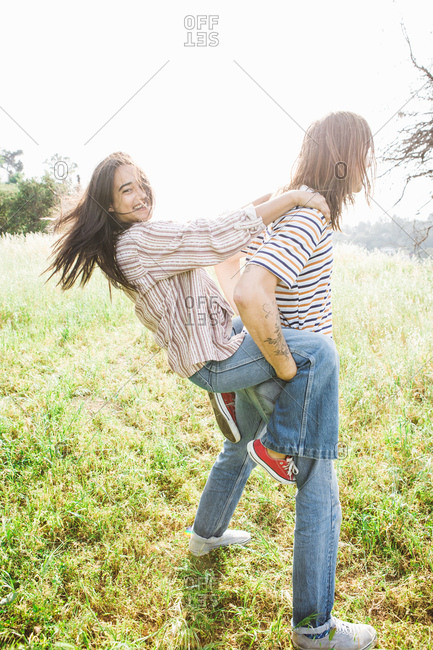 Man giving woman a piggy back ride in a field