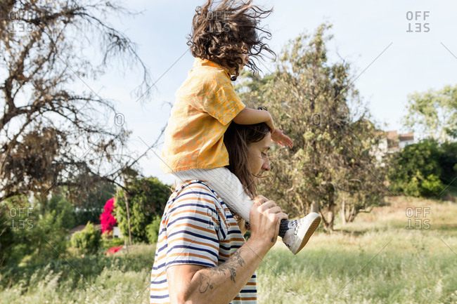 Side view of man carrying young child on his shoulders outdoors