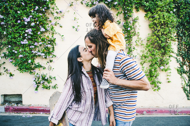 Child on father's shoulders watches parents kiss