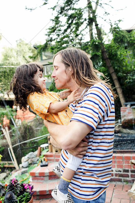 Child leans away from father as he playfully tries to give a kiss