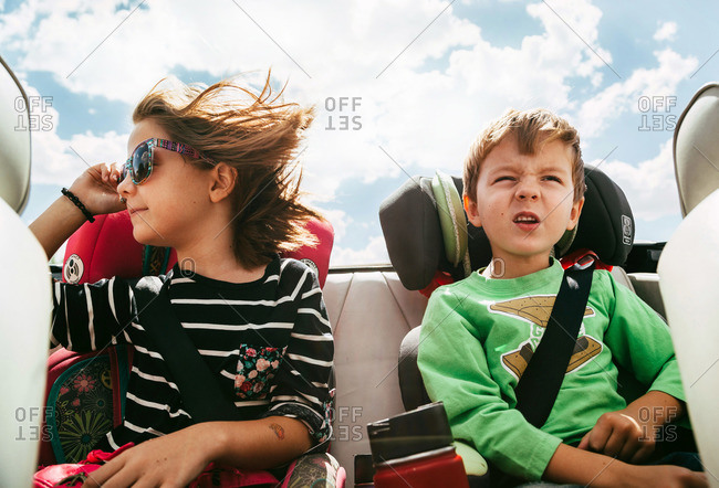 Boy and girl riding in back of open top car