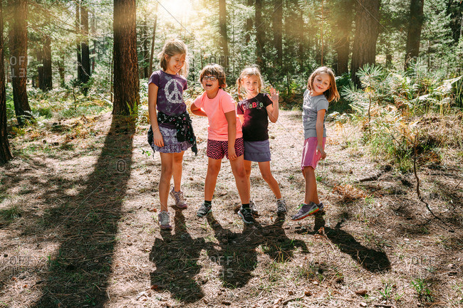 Four girls laughing in summer woods