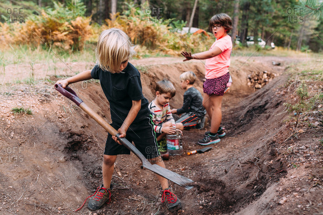 Kids digging in a ditch in forest