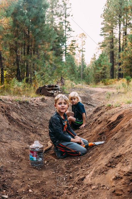 Two kids digging in ditch in woods