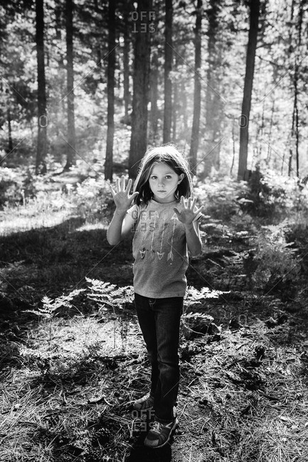 Girl standing in woods showing her palms