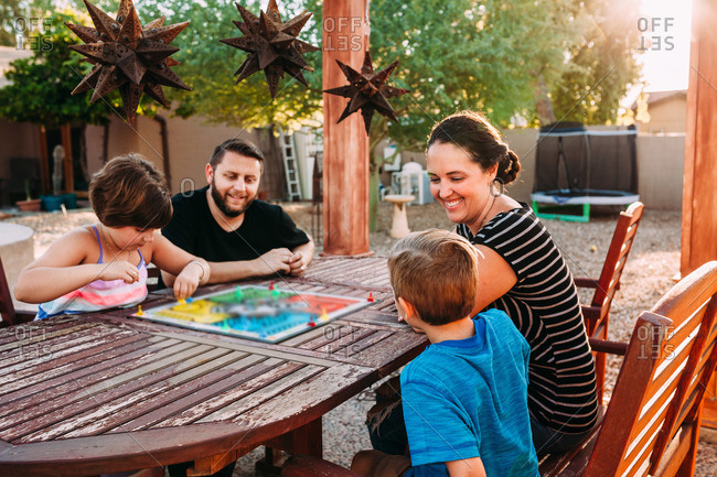 Family gathered around patio table playing board game