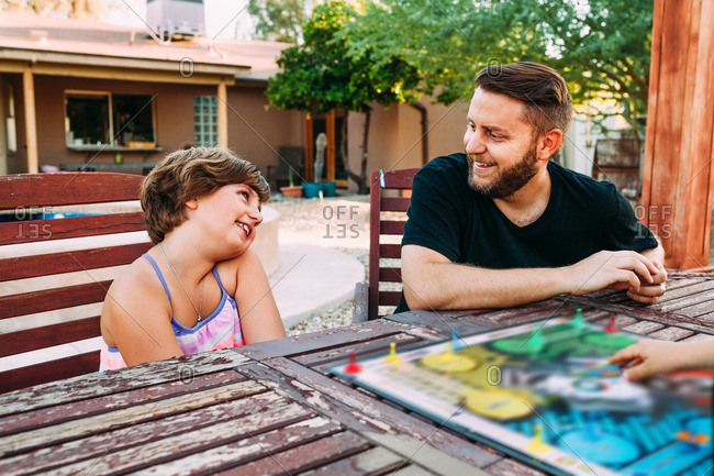 Loving dad and daughter at patio table playing board game