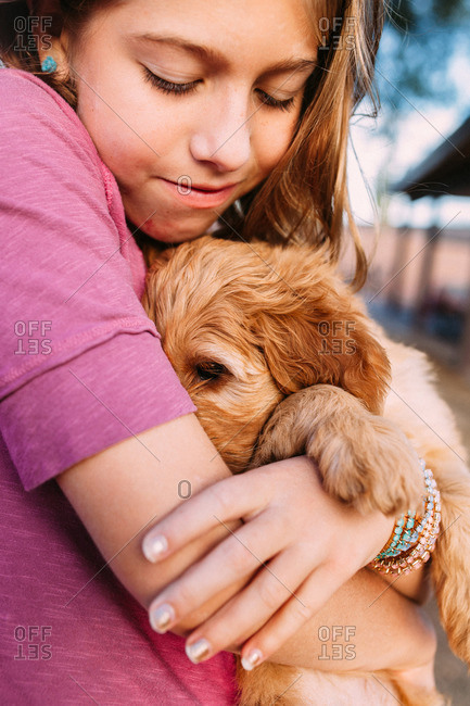 Girl cuddling a soft puppy