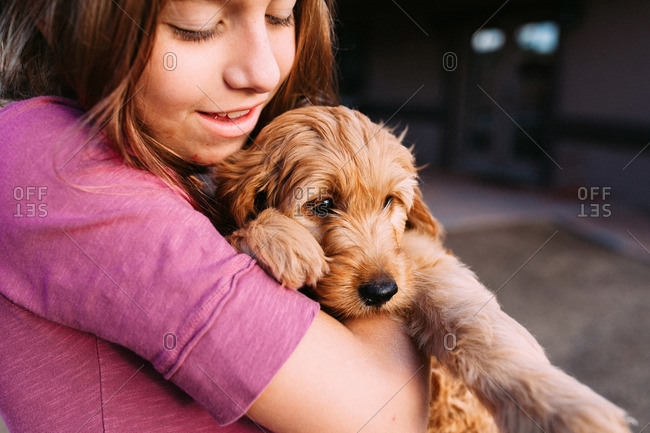 Girl holding a soft puppy
