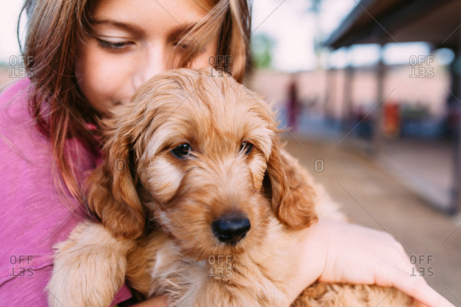 Girl holding a soft puppy outside