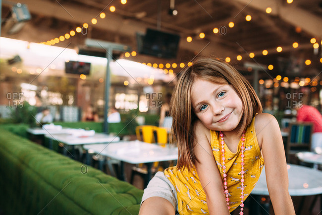 Smiling girl in an outdoor restaurant patio
