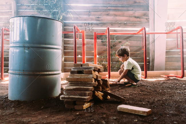 Boy playing with large wood blocks in dirt