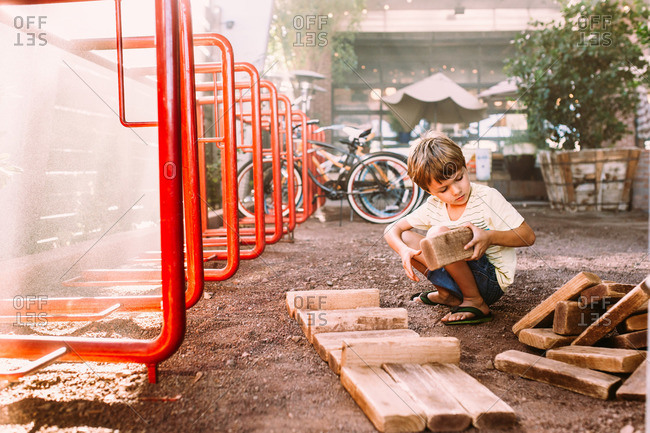 Boy playing with big wood blocks in dirt