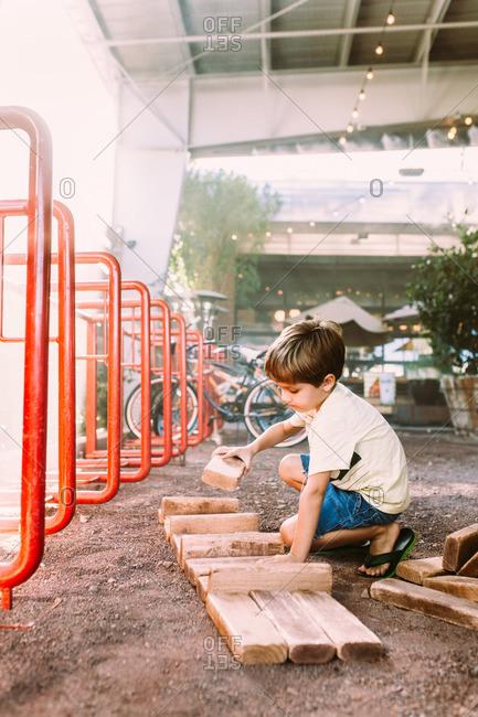Boy playing with big wood blocks outside