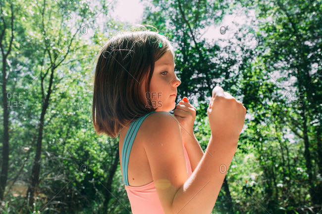 Girl standing in woods making fists