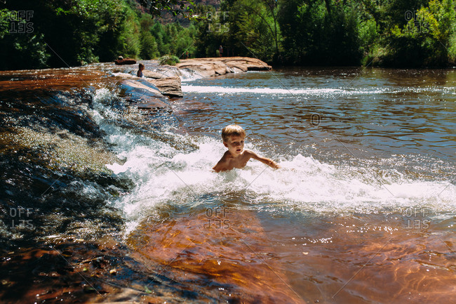 Boy swimming against current in river